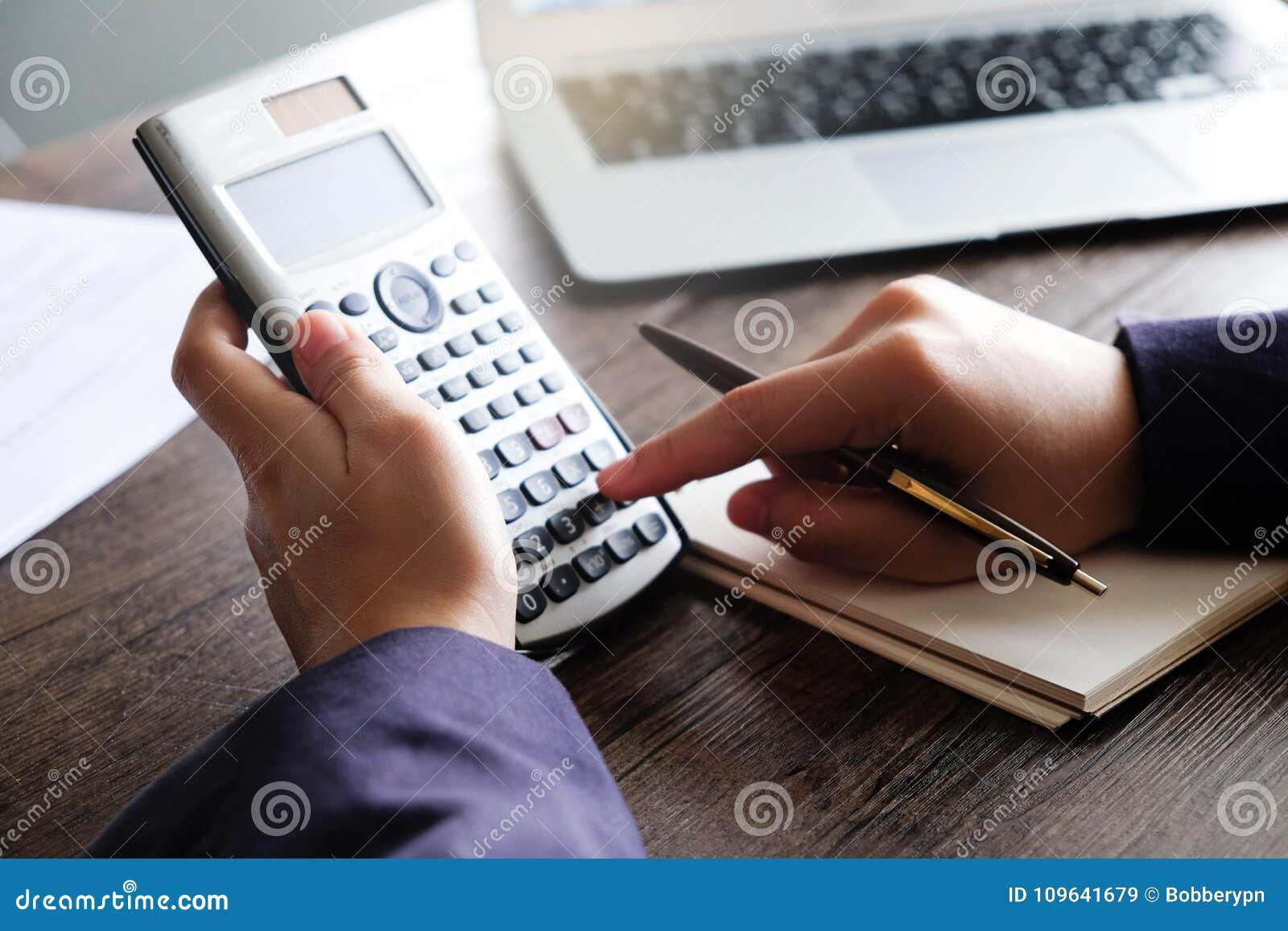 Feche acima do homem da mão que faz finanças e calcule na mesa sobre o escritório do custo em casa Economias, finanças e conceito