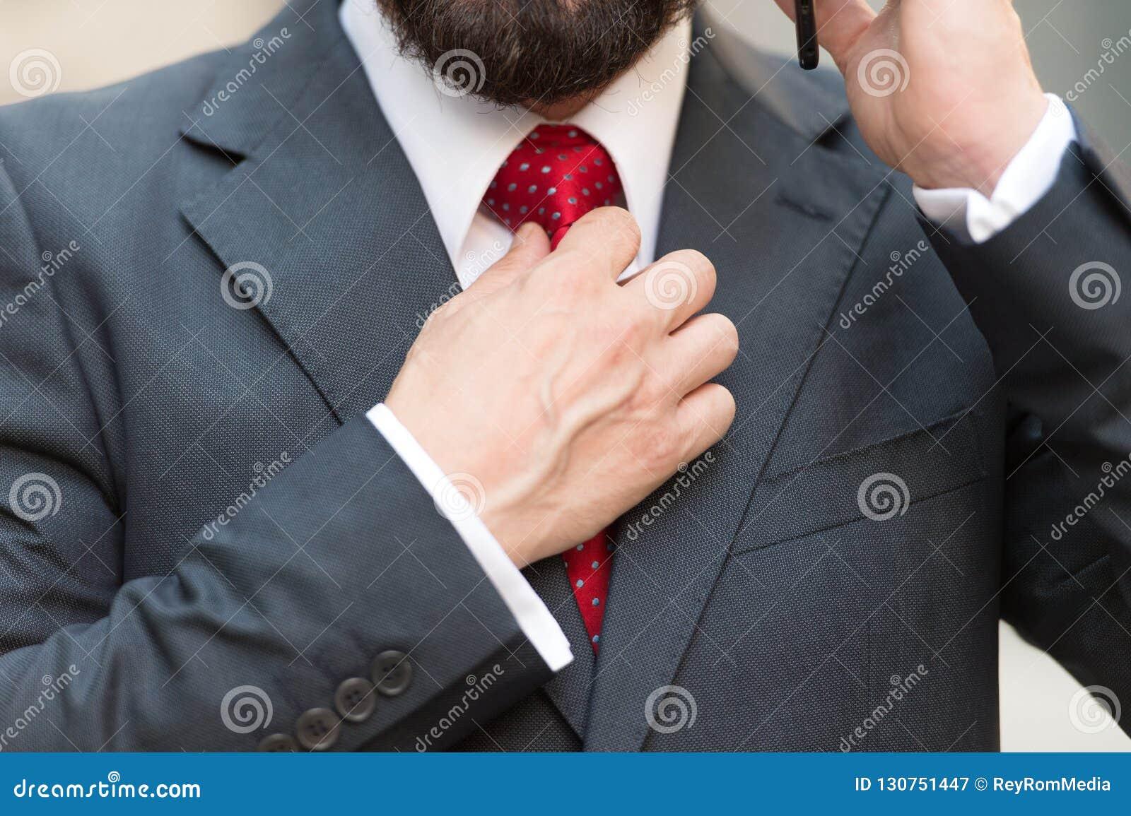 Feche acima do homem farpado que toca no laço vermelho ao falar no telefone