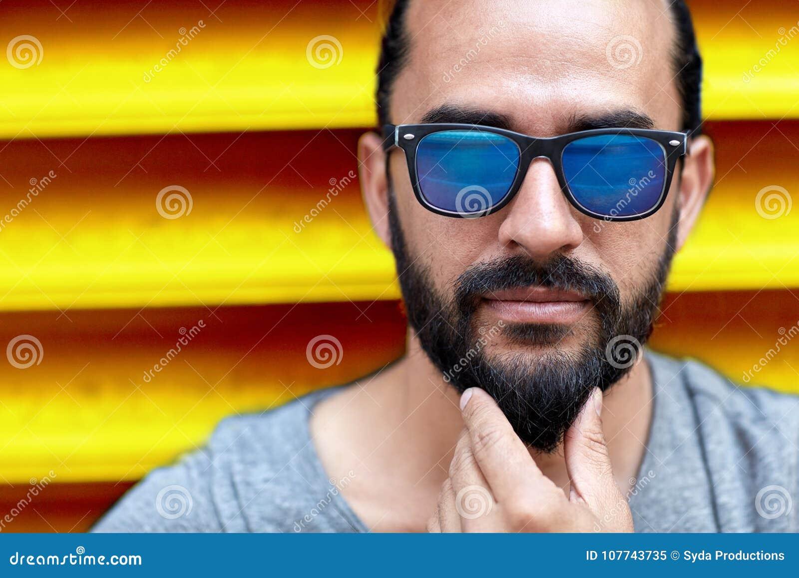 Conceito da forma, do estilo, do eyewear e dos povos - próximo acima do  homem nos óculos de sol que tocam na barba sobre fundo amarelo com nervuras  da ... 86b15647fa