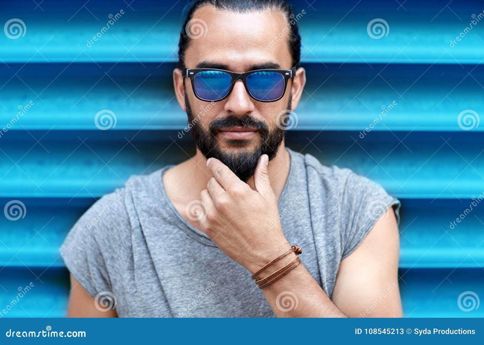 Conceito da forma, do estilo, do eyewear e dos povos - próximo acima do  homem nos óculos de sol que tocam na barba sobre fundo azul com nervuras da  parede b60d6943a8