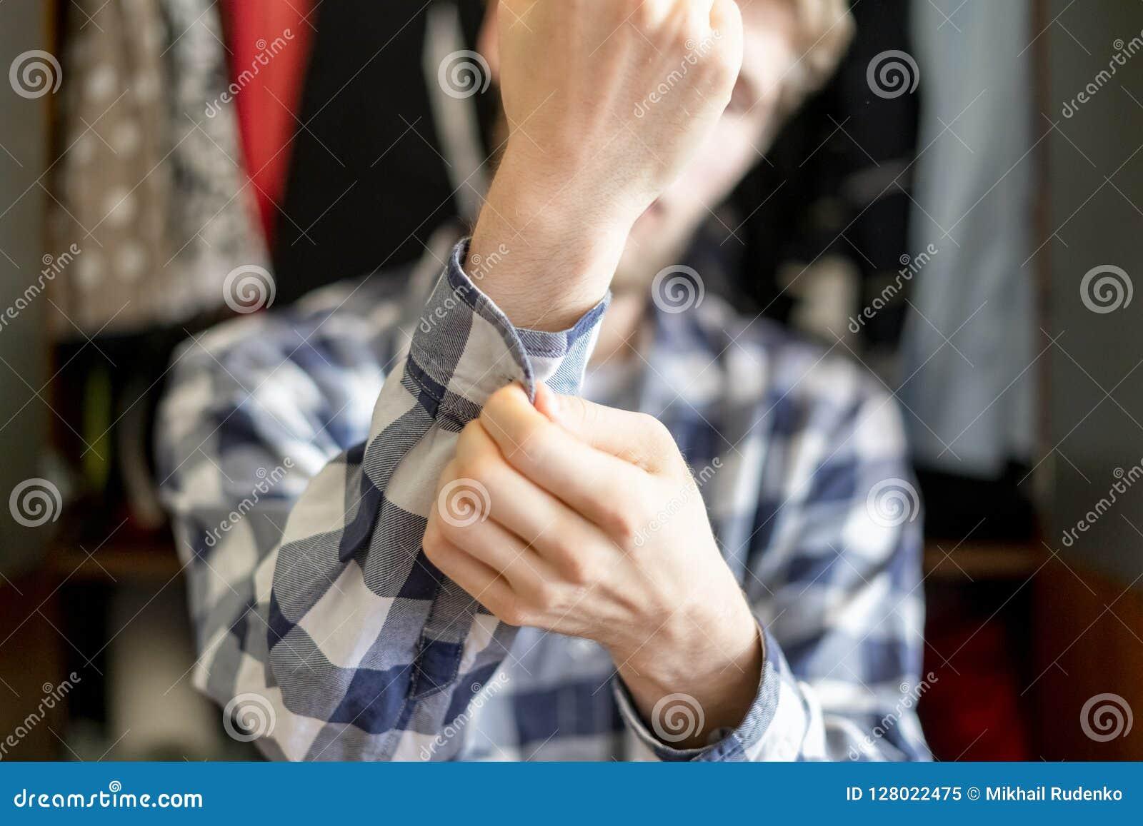 Feche acima do homem novo posto sobre a camisa ocasional em casa, ajustando um botão o fim da luva acima de f