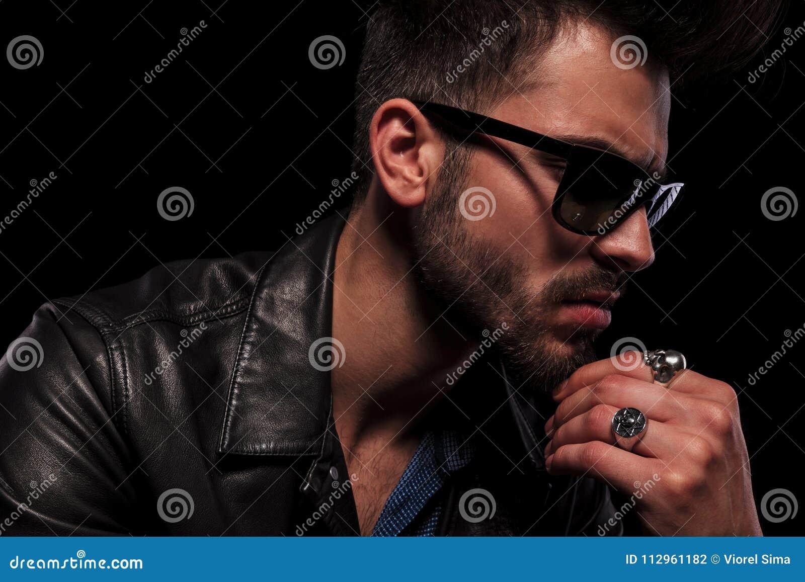 Feche acima do homem pensativo da forma com o casaco de cabedal e os óculos  de sol que olham para baixo para tomar partido, no fundo preto 640c8d6668