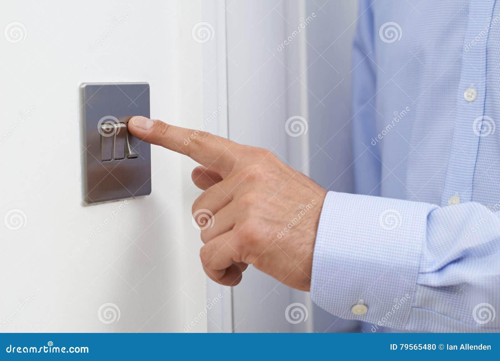 Feche acima do homem que desliga o interruptor da luz