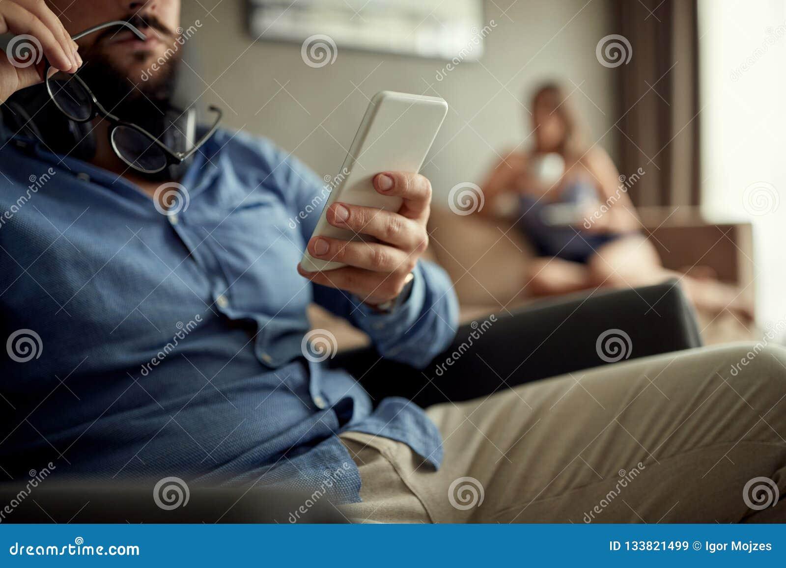 Feche acima do homem que usa um smartphone ao descansar em casa