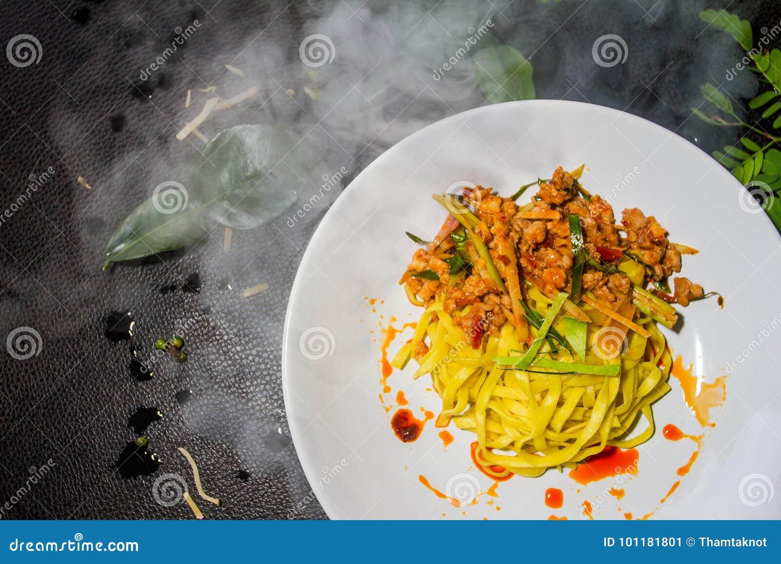 Feche acima do macarronete amarelo fritado de Tom yum, placas brancas arranjadas em um fundo preto Alimento tailandês tradicional