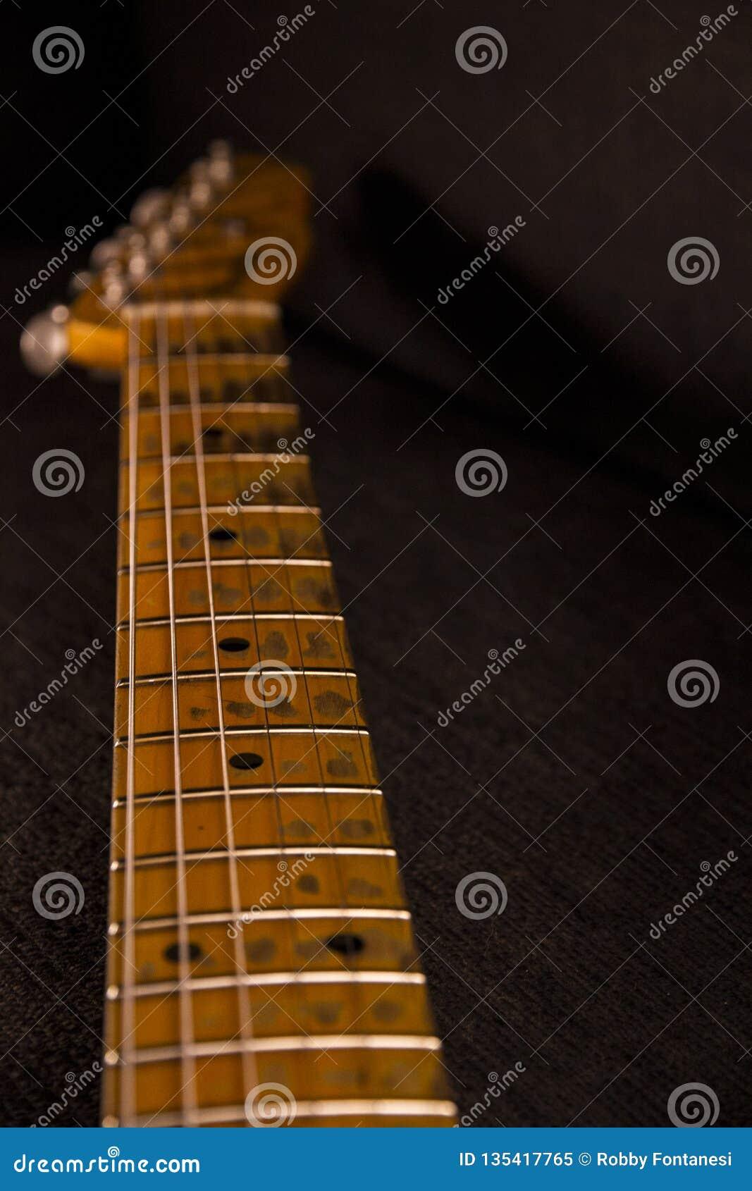 Feche acima do punho da guitarra elétrica com chaves afiado e descascado do uso