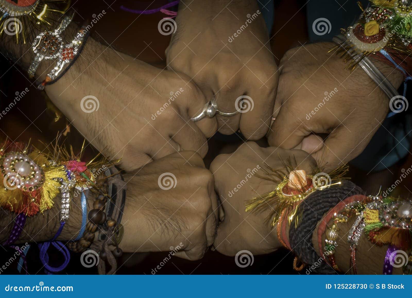 Feche acima do punho da mão dos amigos de meninos humanos que acautelam-se a faixa da amizade nos braços Expressão segura cel da