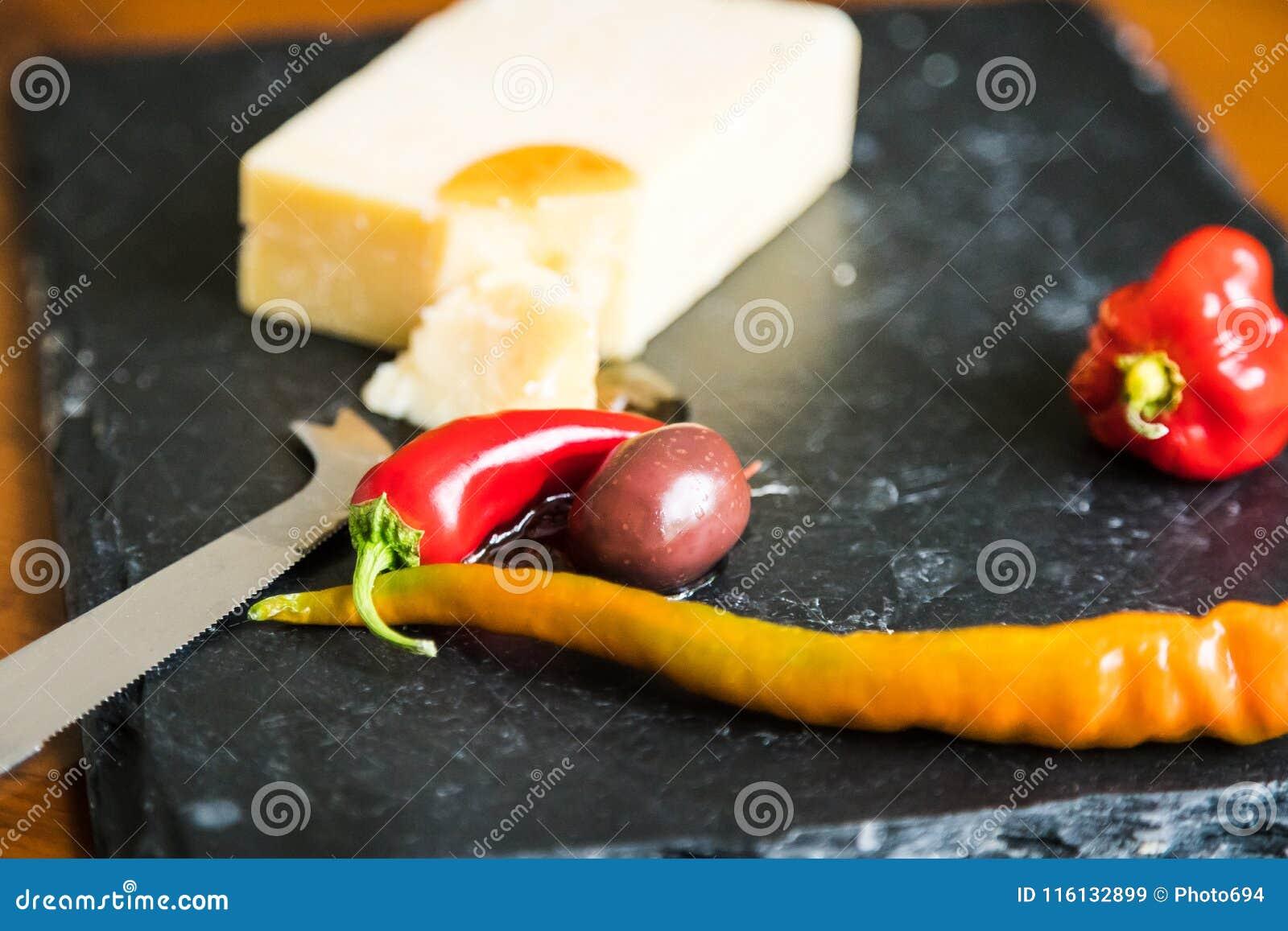 Feche acima do queijo cheddar, da pimenta vermelha e da azeitona na ardósia