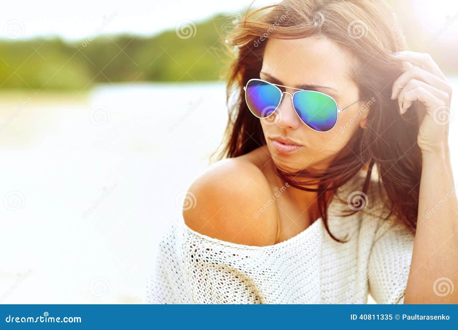 Feche acima do retrato bonito da mulher da forma dos óculos de sol vestindo