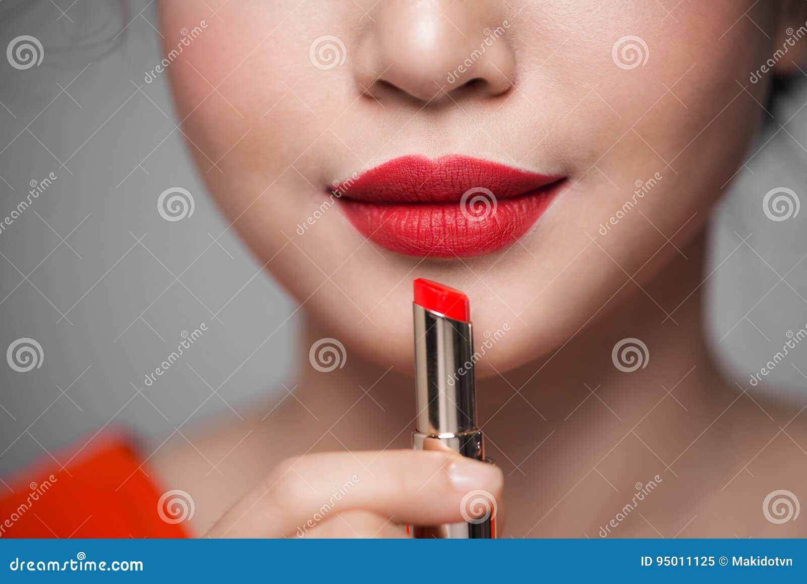 Feche acima do retrato da menina atrativa que guarda o batom vermelho sobre g