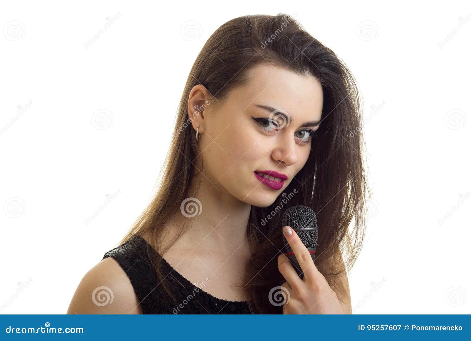 Feche acima do retrato da moça bonita com compõem e microfone nas mãos