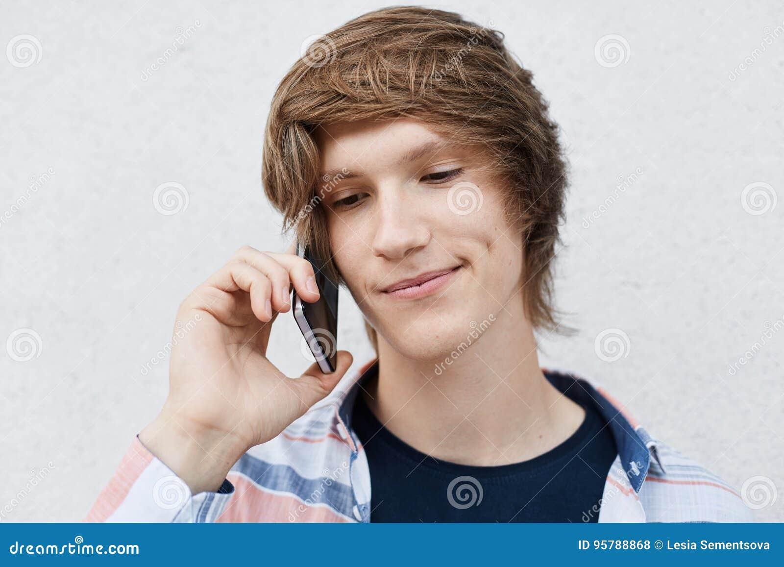 Feche acima do retrato do menino novo considerável com os olhos escuros estreitos, penteado à moda, ondulação no mordente que gua