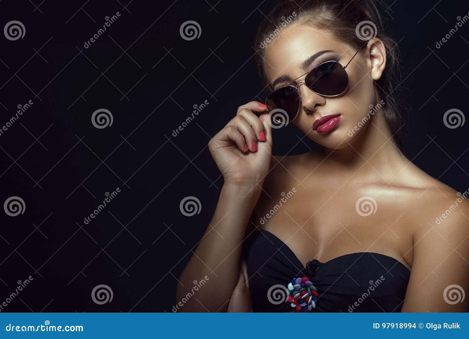 O fim acima do retrato do modelo bronzeado lindo novo com cabelo ocasional  do updo e bonitos compõem óculos de sol na moda vestindo do aviador Isolado  no ... 854d059a79