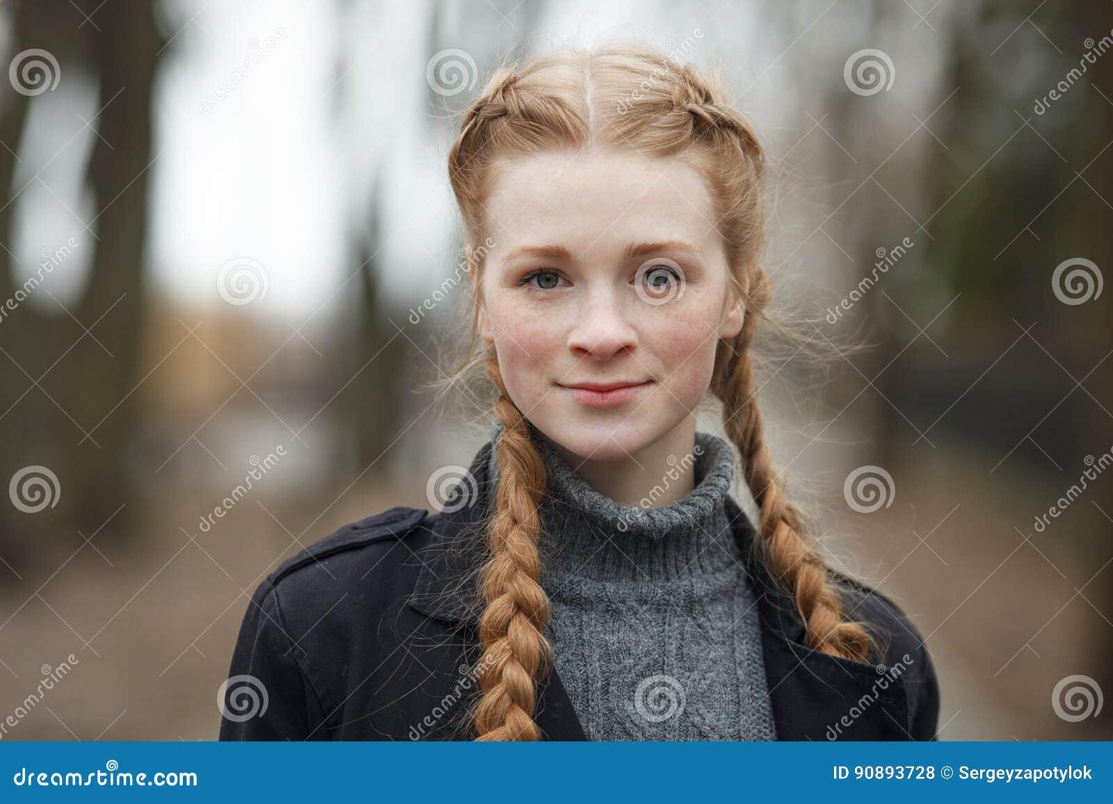 Feche acima do retrato emocional da mulher bonita feliz com o cabelo das tranças do vermelho e a composição natural que vestem o