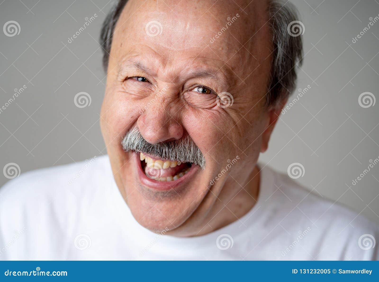 Feche acima do retrato do homem superior de sorriso com a cara feliz que olha a câmera