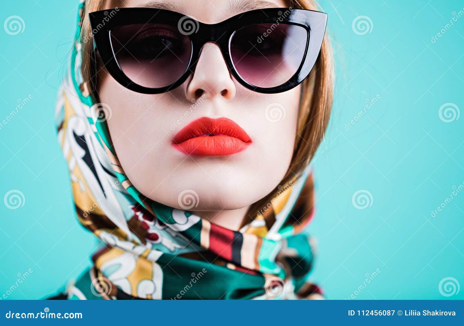 Feche acima do tiro da jovem mulher à moda nos óculos de sol contra o fundo 58e5604acd