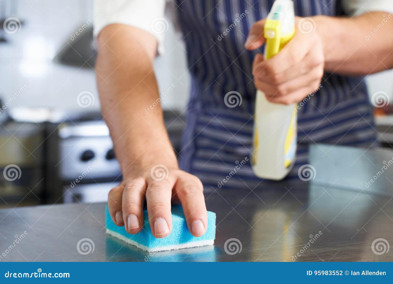 Feche acima do trabalhador na cozinha do restaurante que limpa para baixo após Ser