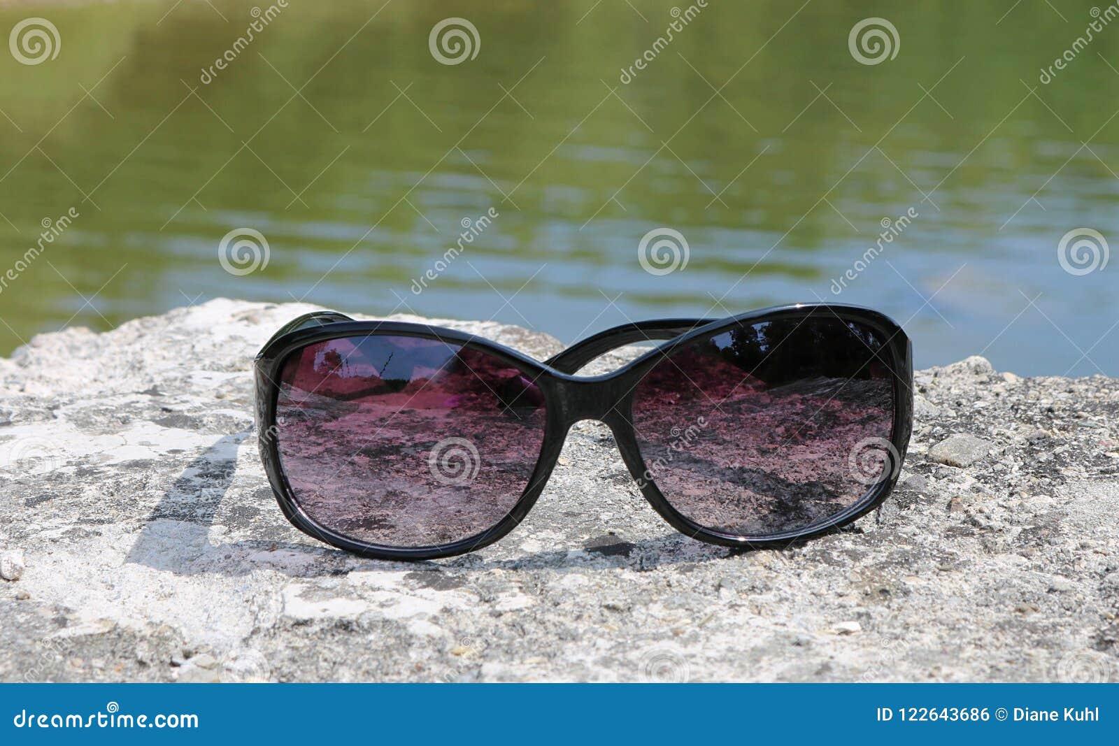 A água azul e verde do rio de Saugeen em Walkerton, Ontário é o fundo para  plástico preto óculos de sol moldados com o matiz malva que descansa na  rocha no ... 5a0b71a0f4