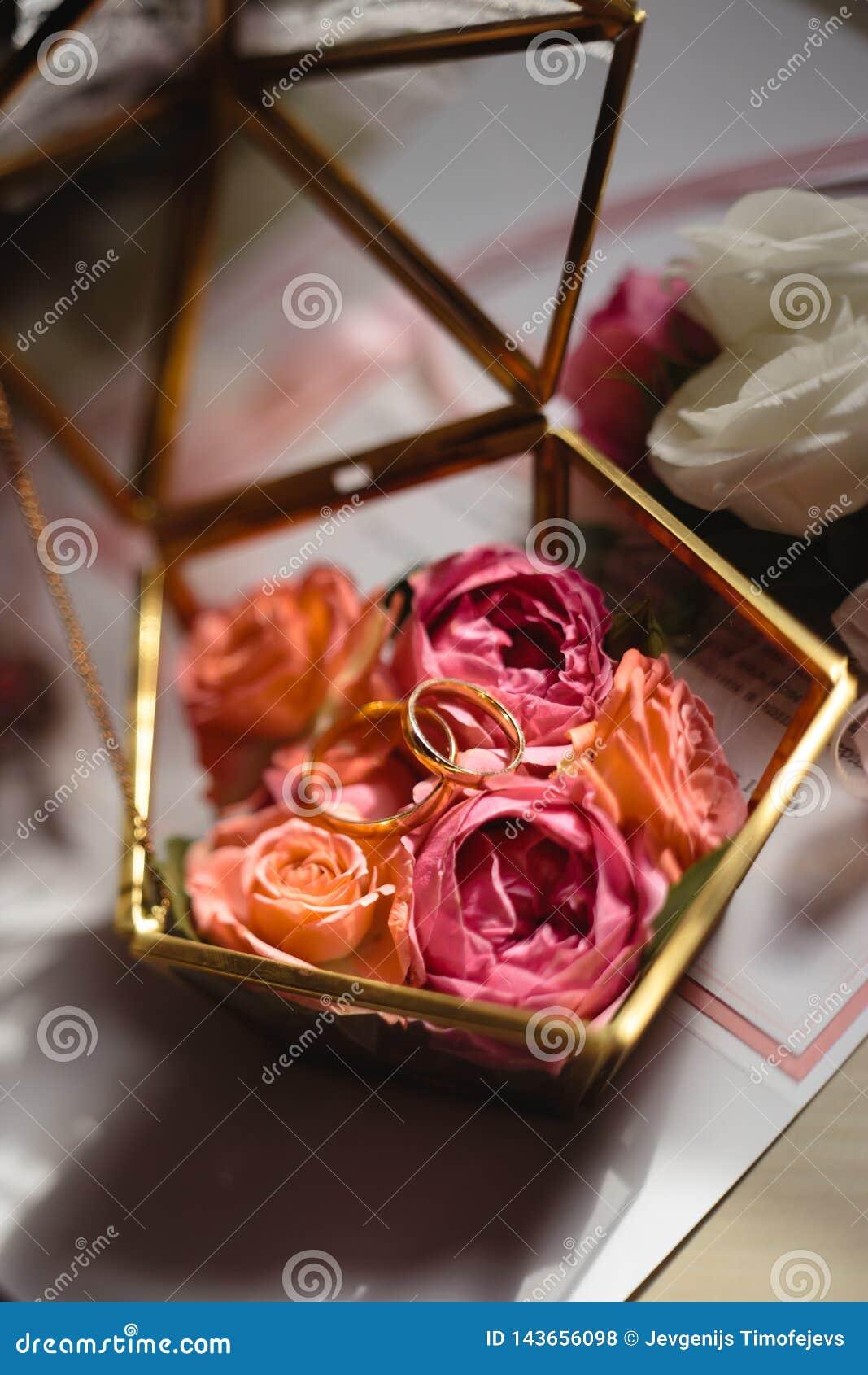 Feche acima dos detalhes reais em um casamento - caixão de vidro das flores para anéis nupciais