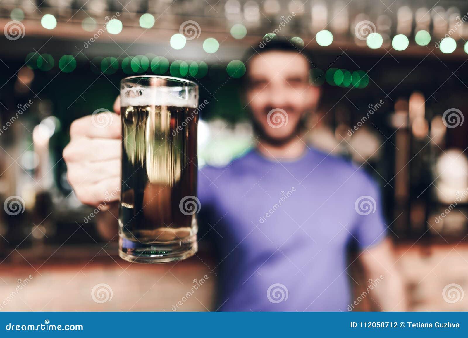 Feche acima dos empregado de bar que guardam o vidro da cerveja na barra de esportes