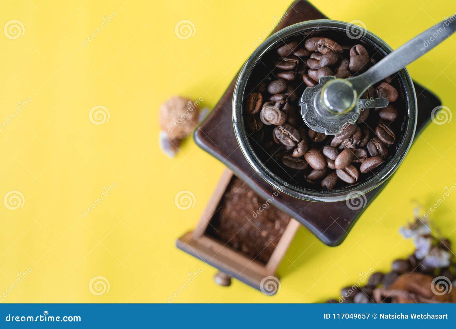 Feche acima dos feijões de café seletivos e do feijão de café sorrido no moedor de café de madeira do vintage no fundo amarelo