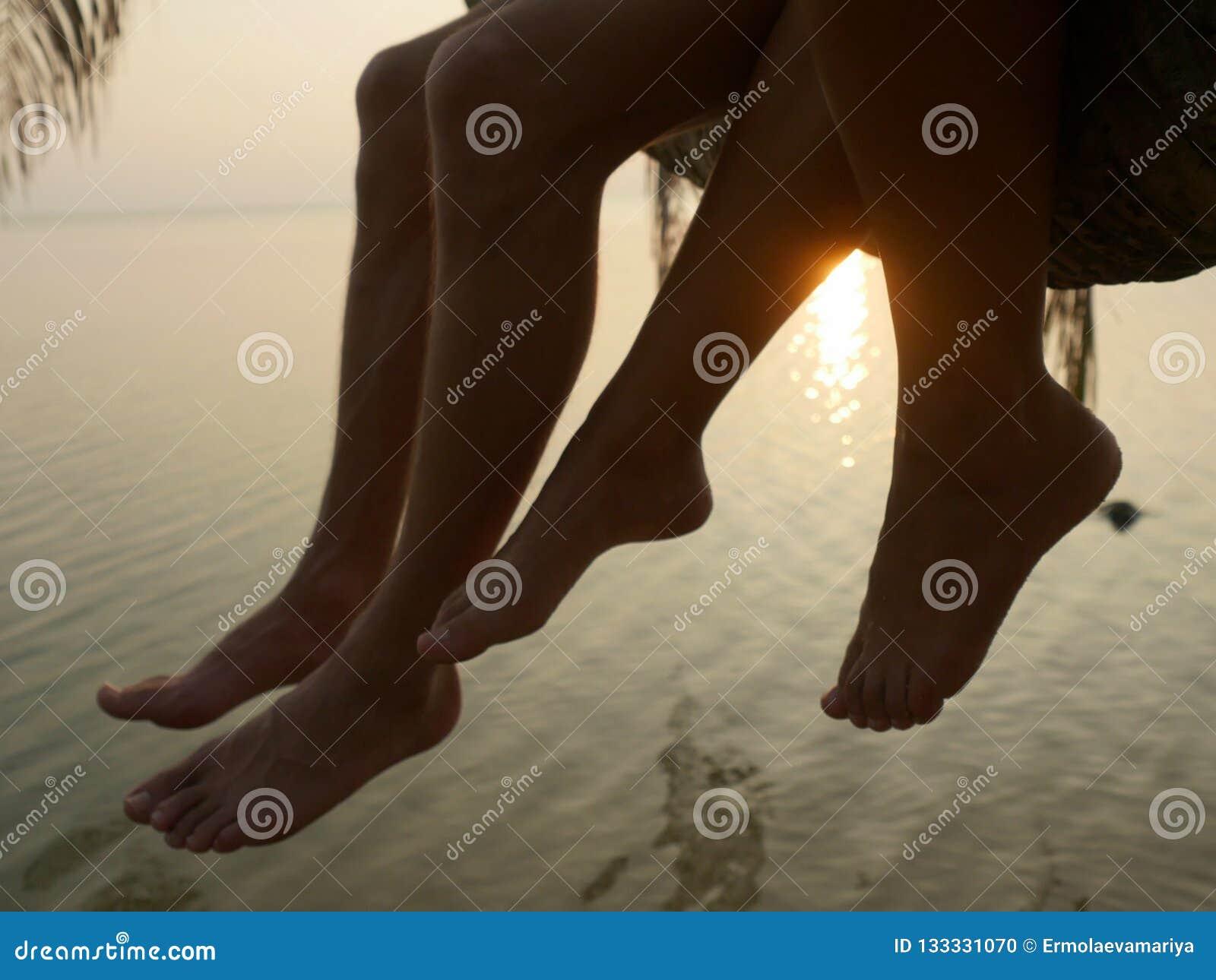 Feche acima dos pés de um par que senta-se em uma palmeira durante o por do sol no litoral