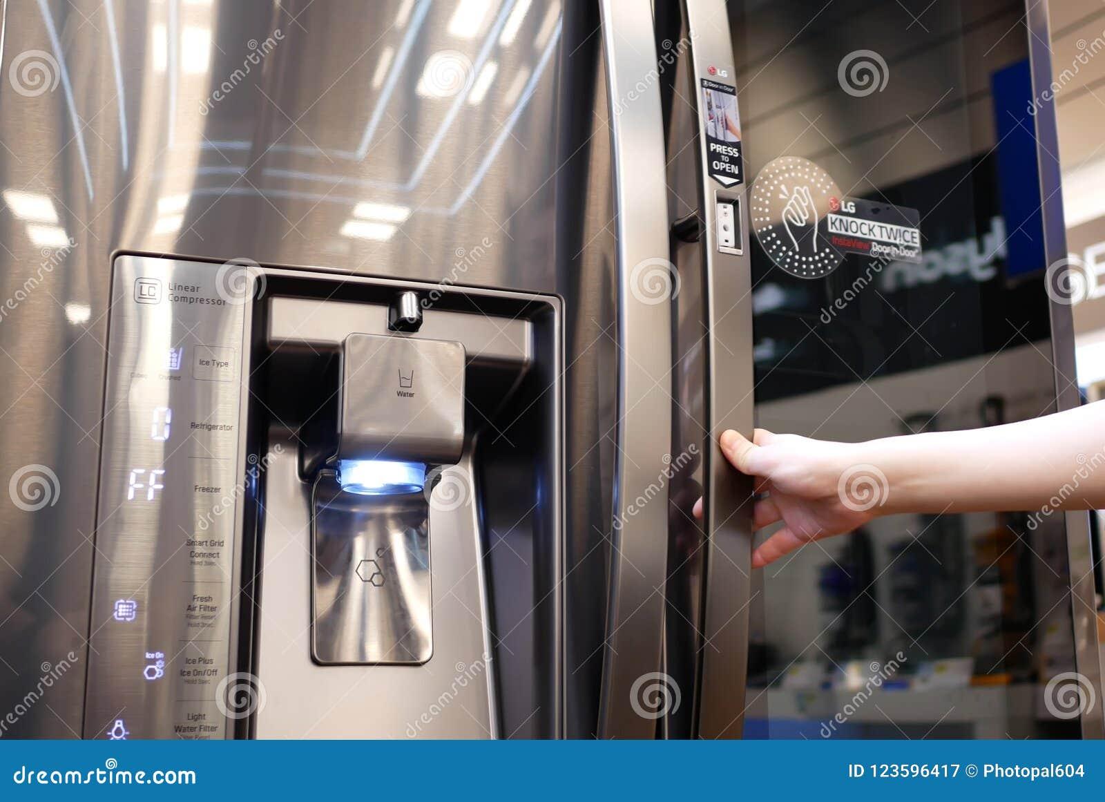 Feche acima dos povos que tentam um refrigerador novo dentro da loja eletrônica