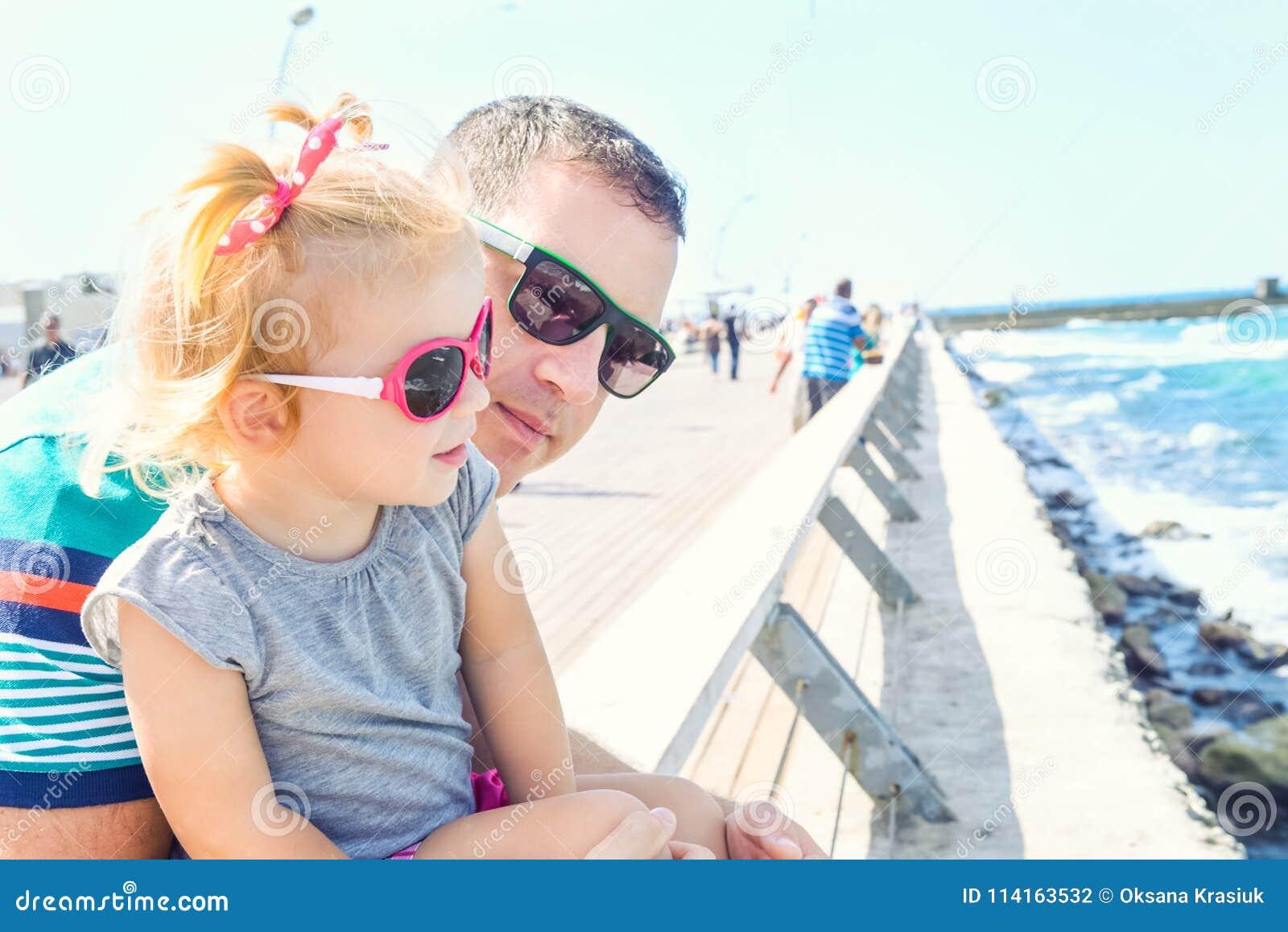 Feche acima dos retratos do pai e da filha pequena nos óculos de sol que  olham 8e56f7dc9a