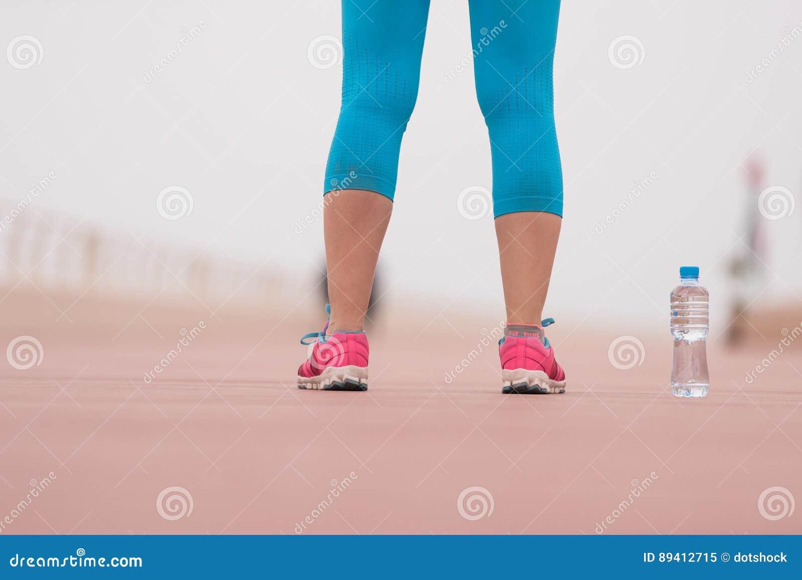 Feche acima em tênis de corrida e em garrafa da água