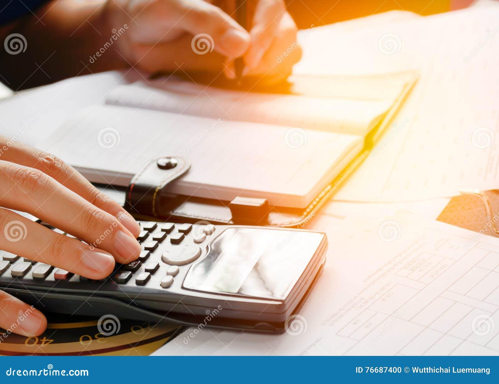 Feche acima, homem de negócio ou contador do advogado que trabalham em contas usando uma calculadora e escrevendo em originais,