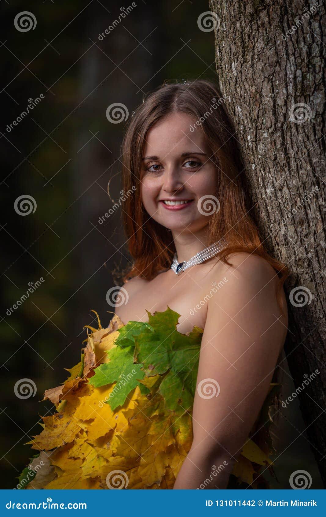 Feche acima na moça bonita com o cabelo longo que inclina-se na árvore, vestindo o vestido feito das folhas coloridas na floresta