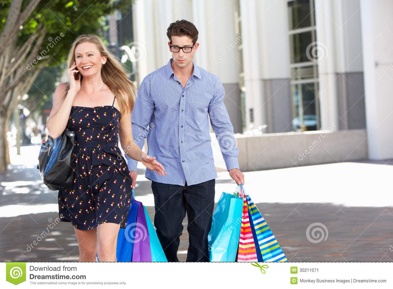 Fed Up Man Carrying Partners Shopping Bags On City Street Stock ...