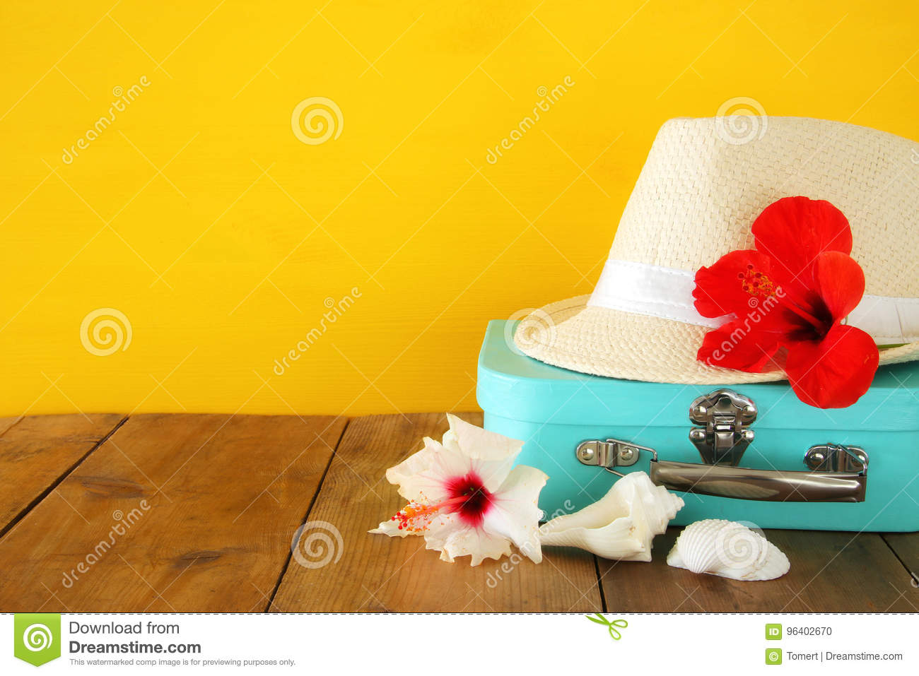 Fedora hat, tropical hibiscus flower on wooden table. relaxation or vacation concept