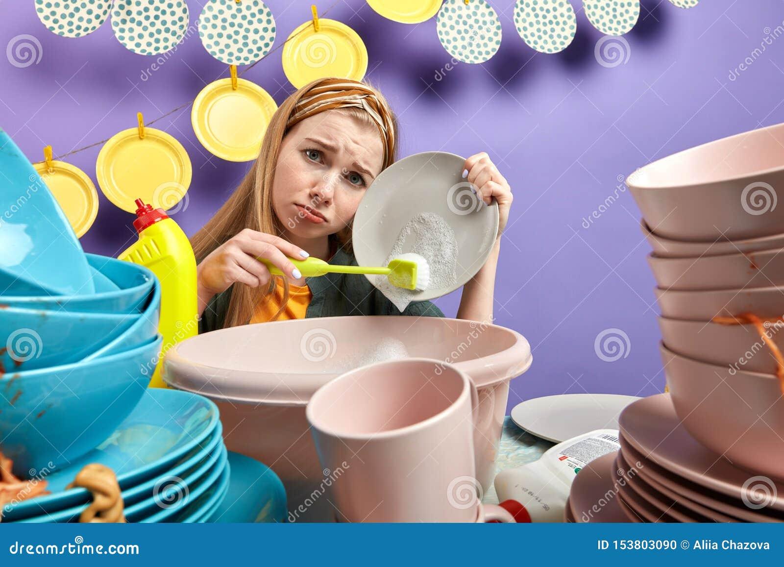 Feds tristes de fille vers le haut du nettoyage et du lavage dans la cuisine avec le mur bleu