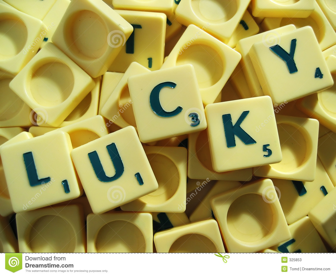Scrabble tiles in a pile with the word 'lucky' spelled out.