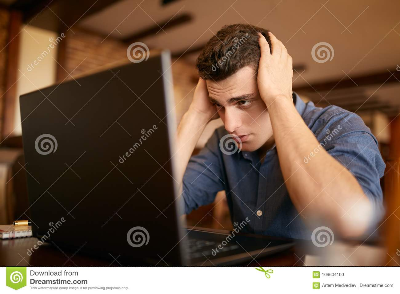 Feeling tired. Frustrated young handsome man looking exhausted and sick while sitting at his working place with laptop