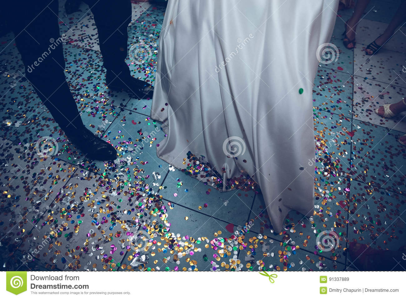 Feet of the bride and groom on a background of confetti