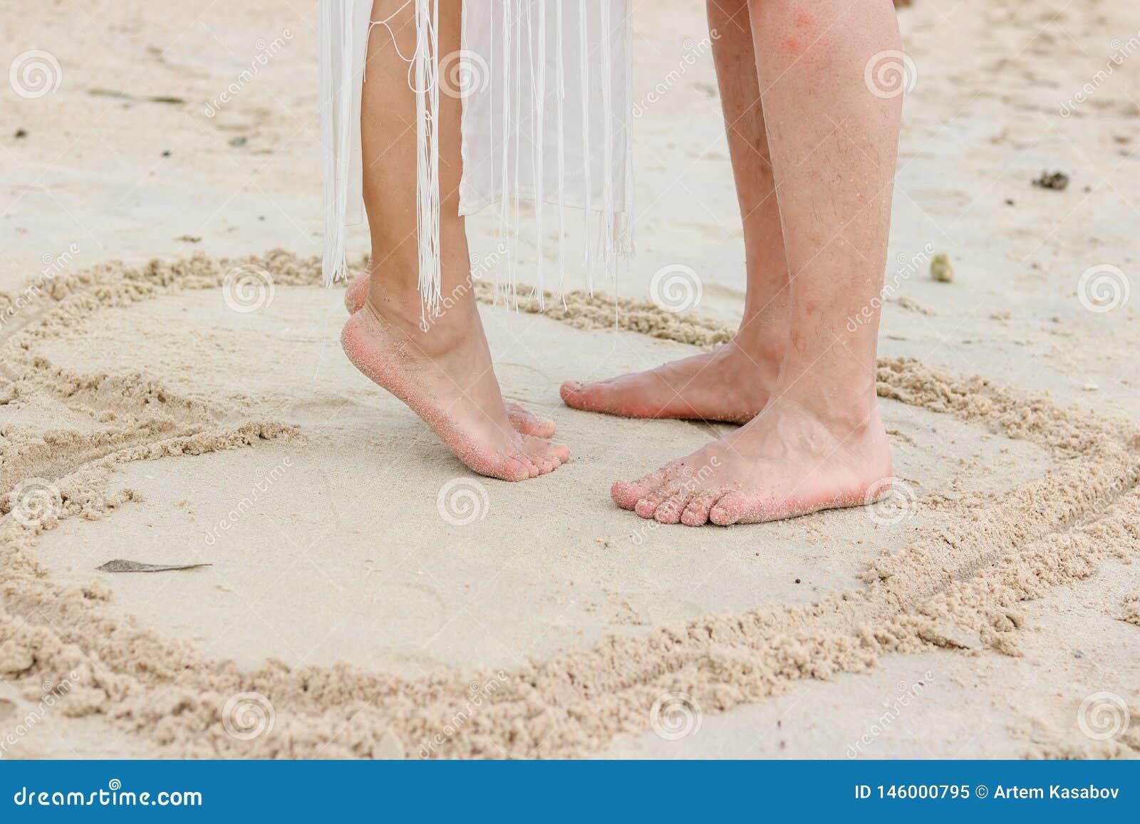 Feet of couple on the beach