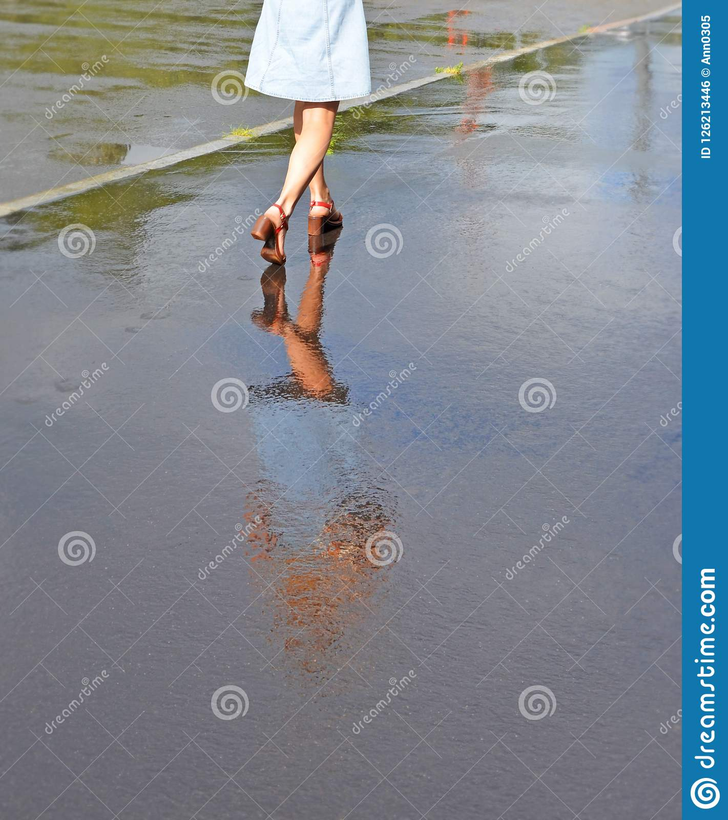 Feet of the girl and her reflection in water on the sidewalk