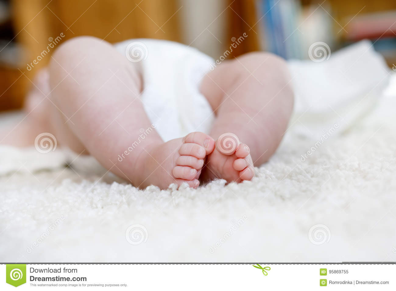 Feet and legs of newborn baby with diaper