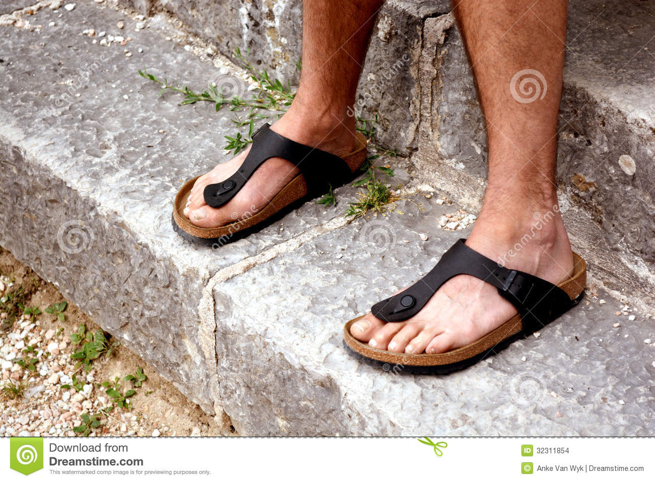 84bf4574ed34 Two Caucasian feet of a monk in black sandals standing on ancient stairs.