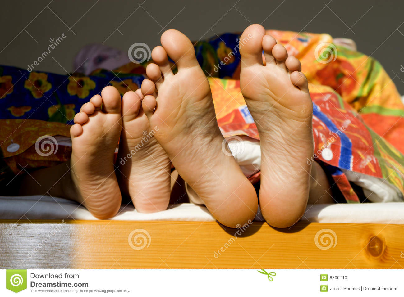 Curious baby looking at mother's feet in bed - Stock Photos ...