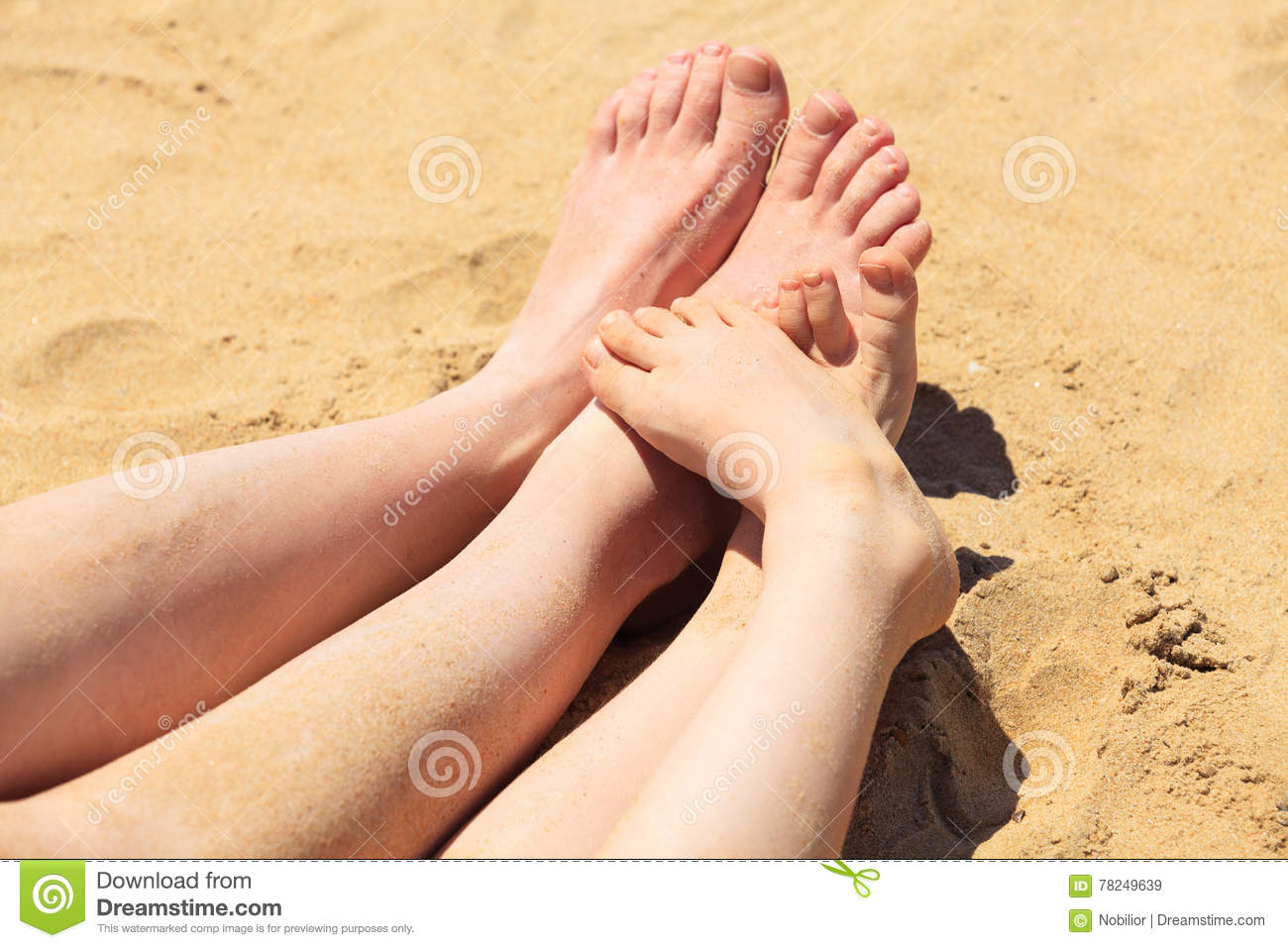 Feet of mother and her child in the sand