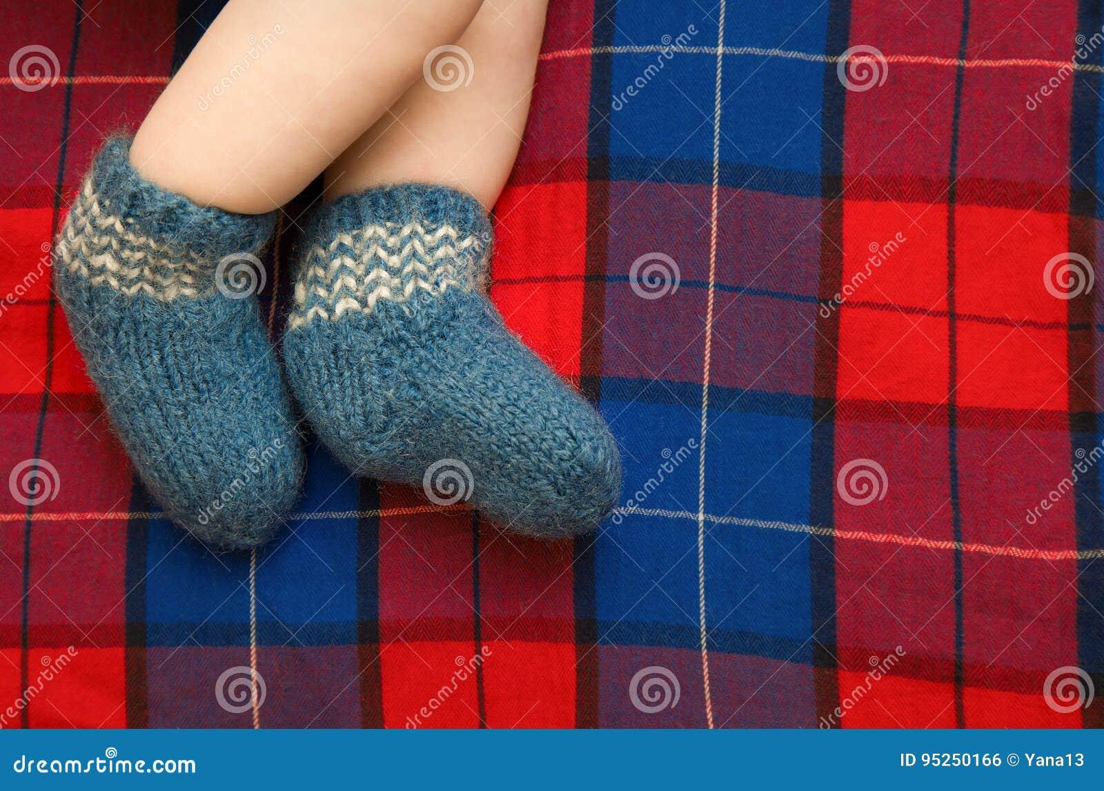 Feet Newborn Baby In A Blue Knitted Woolen Socks On The Backgrou