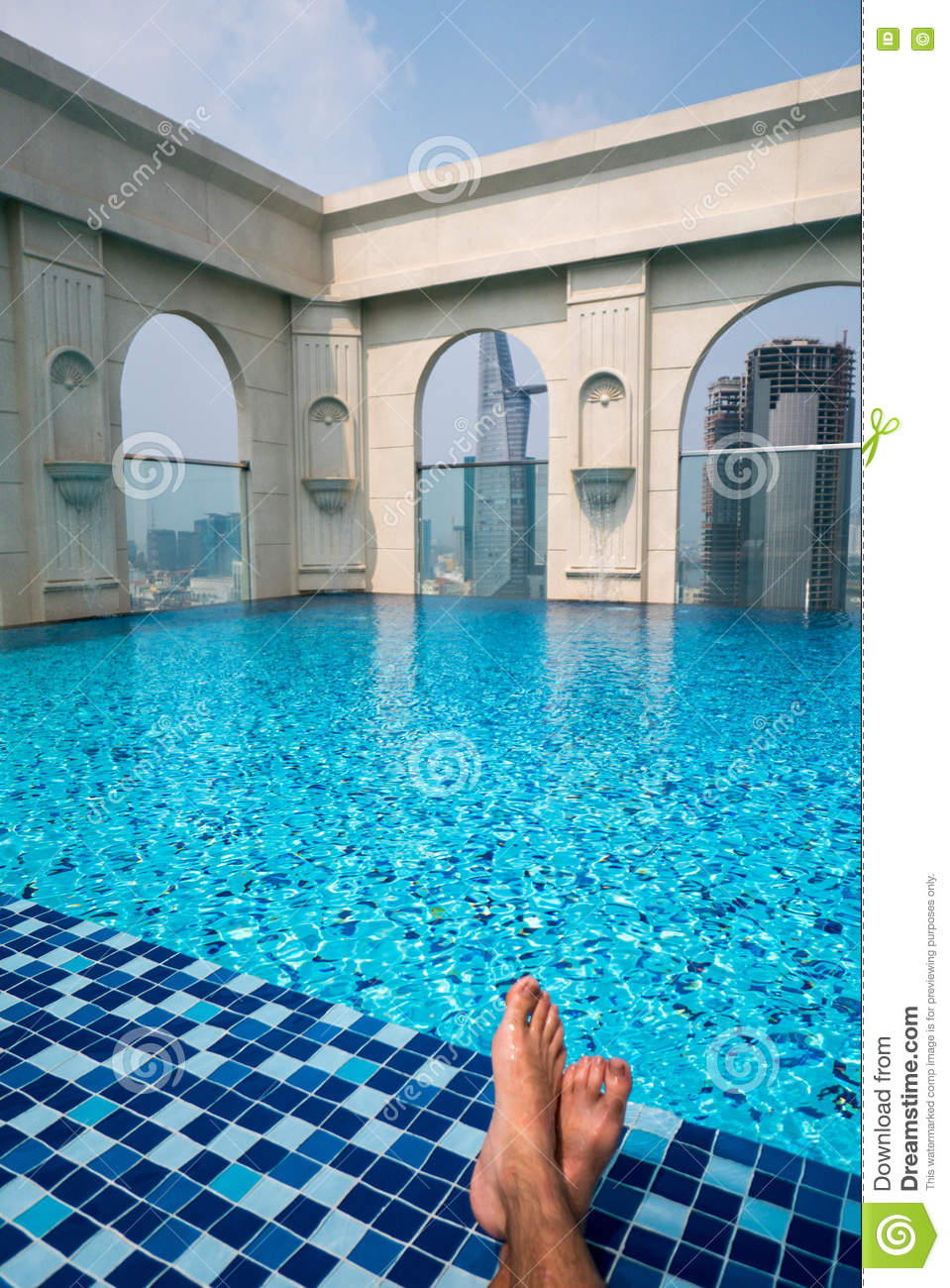 Pool On Top Of Building : Feet over the sparkling pool on top of building with