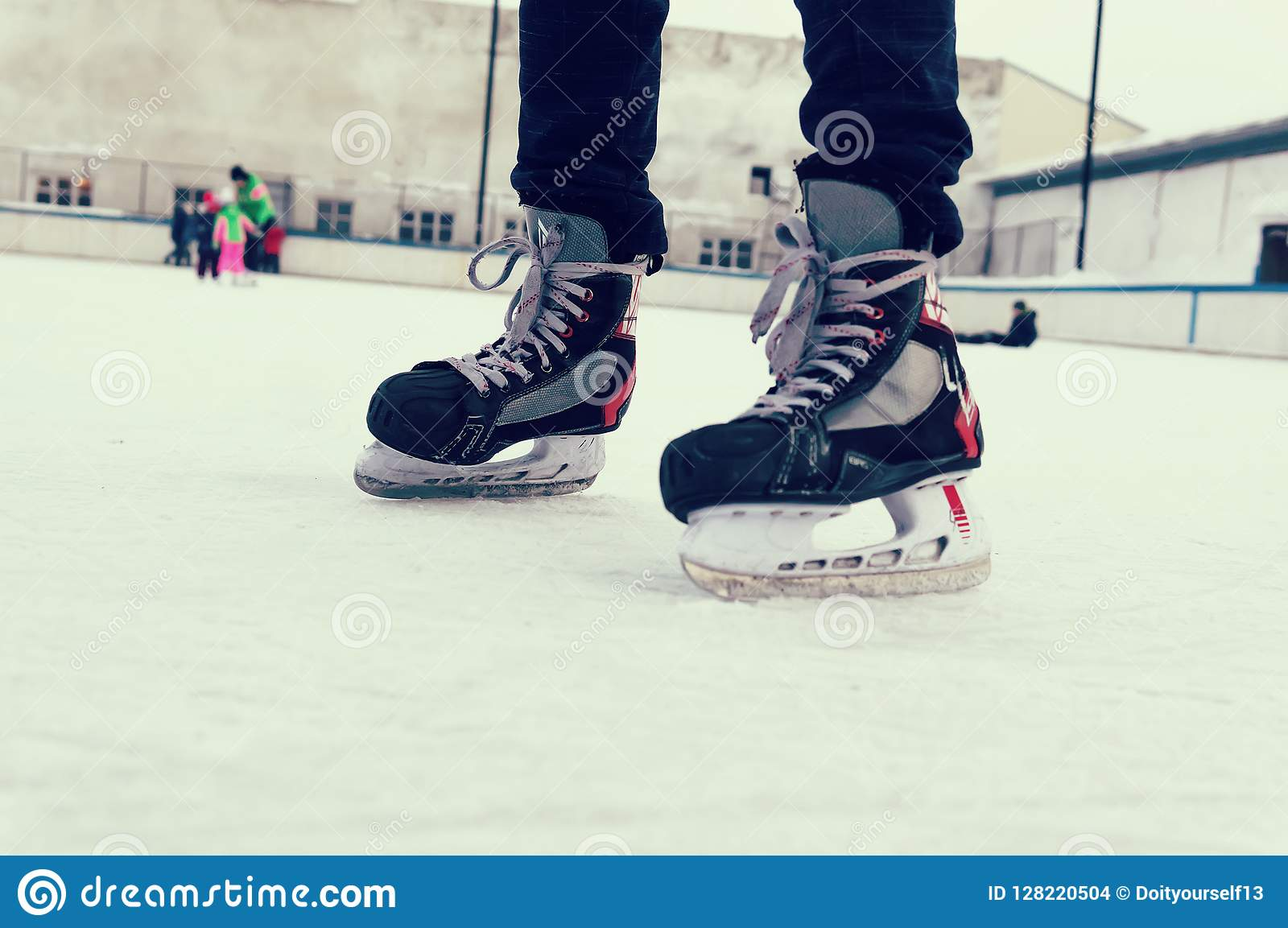 Feet On The Skates Of A Person Rolling On The Ice Rink Stock Photo
