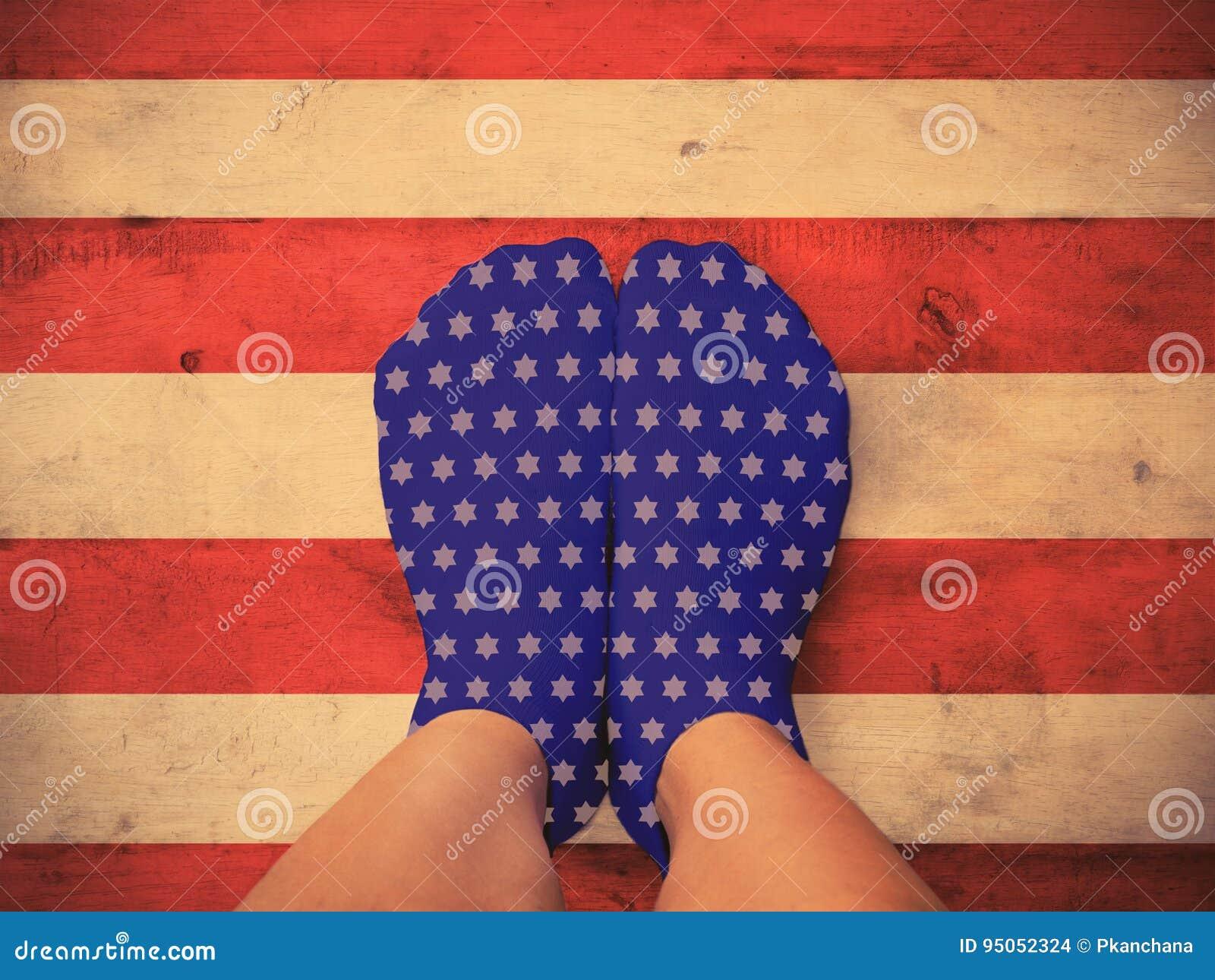 Feet wearing blue socks with white star shape on wooden floor