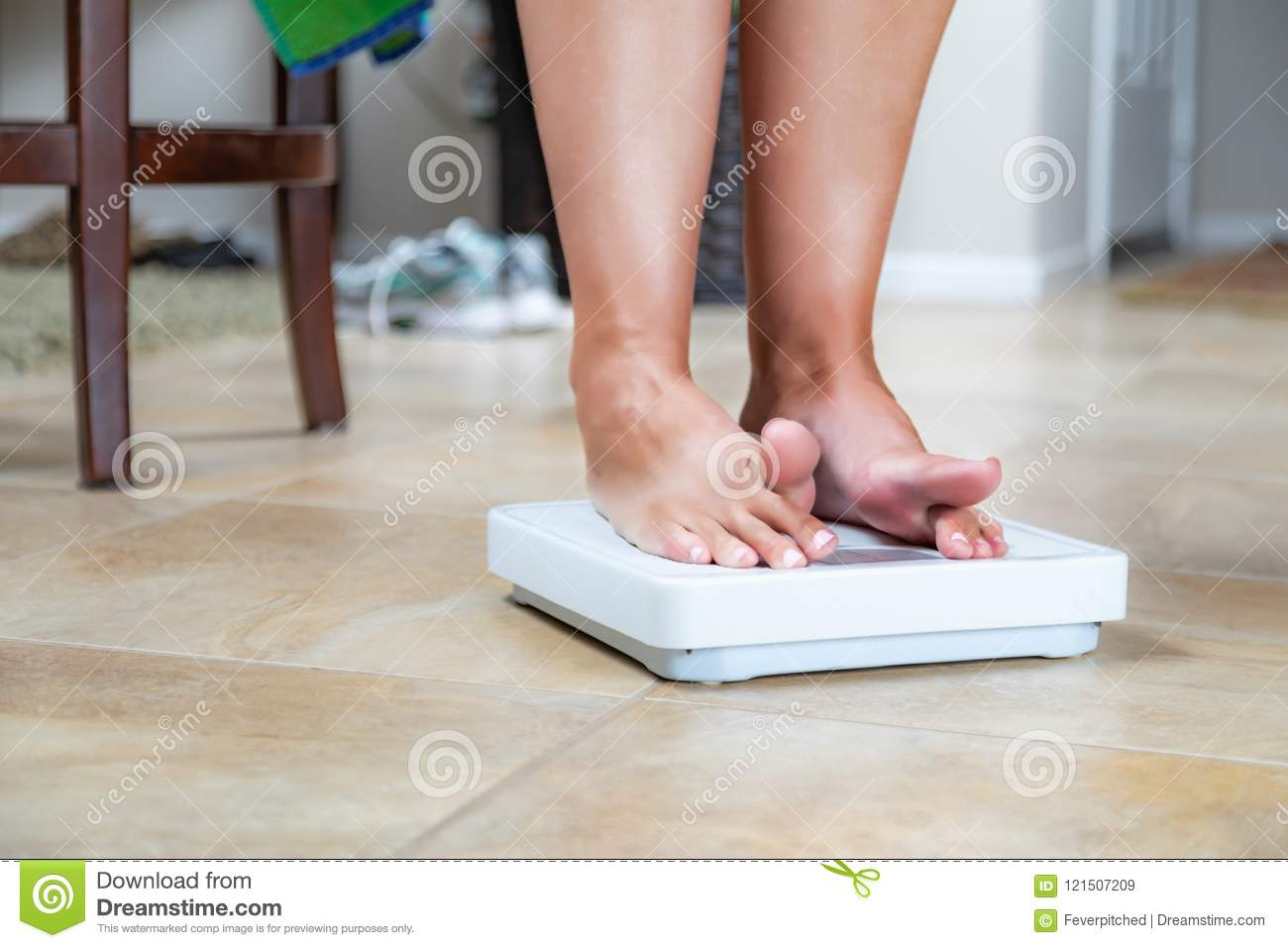 Woman Standing On Weighing Scales High-Res Stock Photo