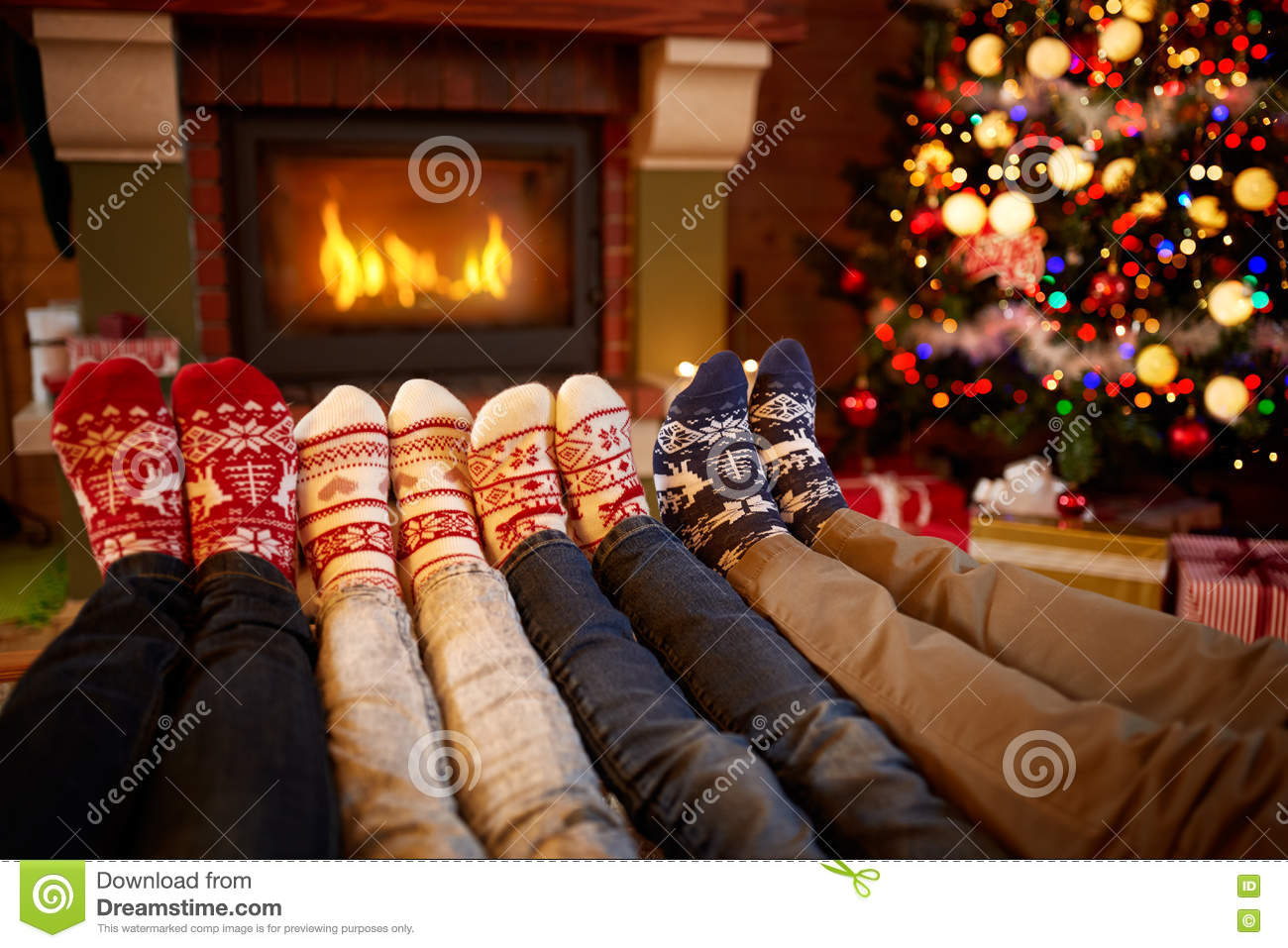 Feet in wool socks near fireplace in Christmas time