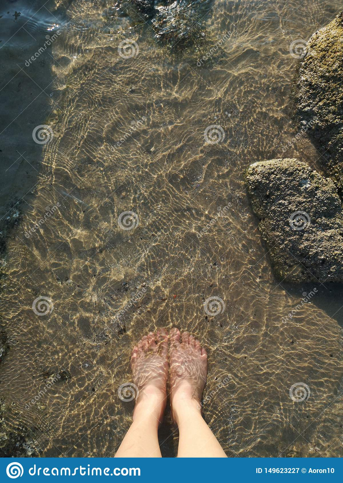 The feet of a young woman dipping into the sea